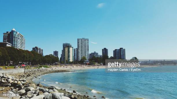 sea by city against clear sky - english bay stock photos and pictures