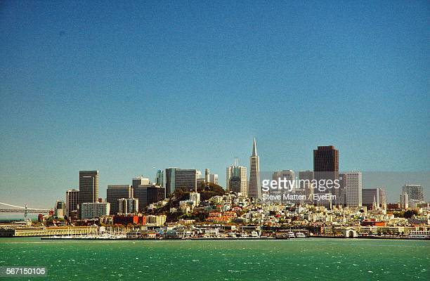 sea by city buildings against blue sky - steve matten stock pictures, royalty-free photos & images