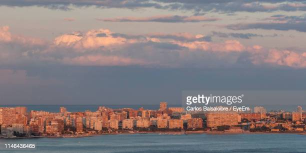sea by city buildings against sky during sunset - bucht stock-fotos und bilder