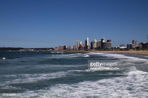 sea by cityscape against clear sky - durban beach stock photos and pictures
