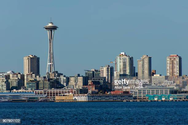 sea by cityscape against clear sky - space needle stock-fotos und bilder