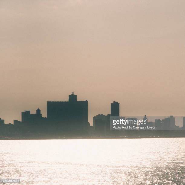 sea by cityscape against sky during sunset - carvajal stock photos and pictures