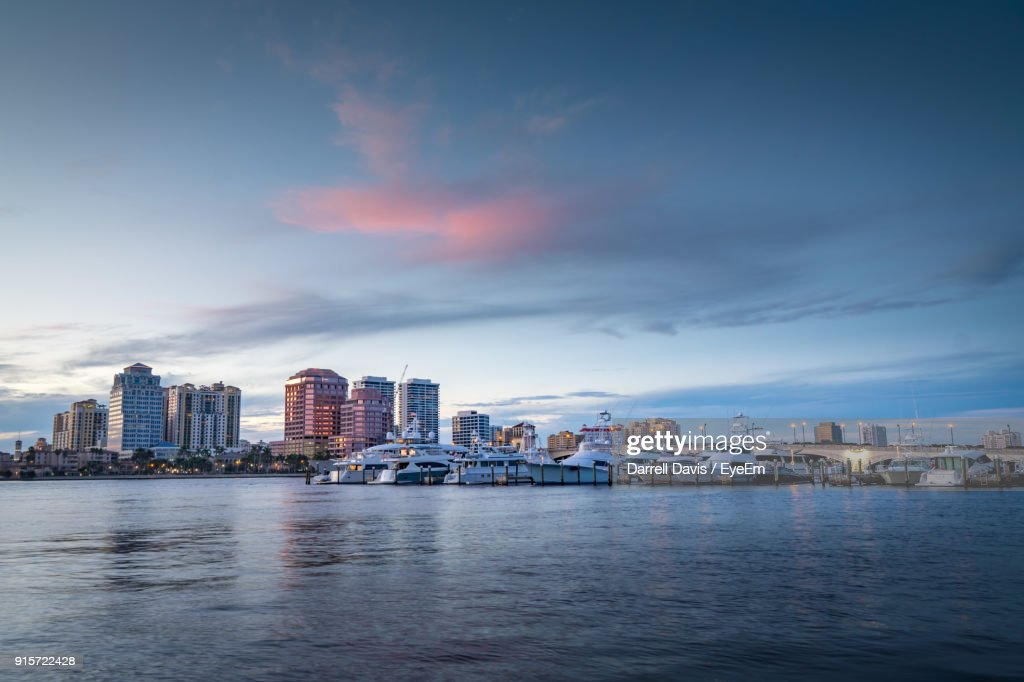 Sea By Cityscape Against Sky During Sunset : Stock Photo