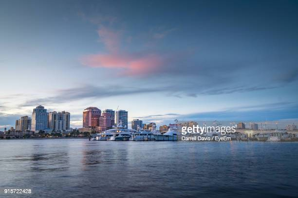 sea by cityscape against sky during sunset - palm beach county stockfoto's en -beelden
