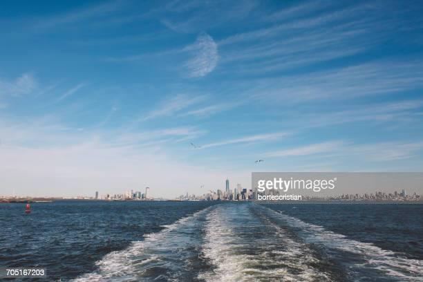 sea by cityscape against sky - bortes foto e immagini stock