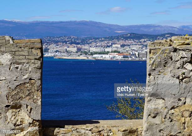 sea by cityscape against sky - hutton stock photos and pictures