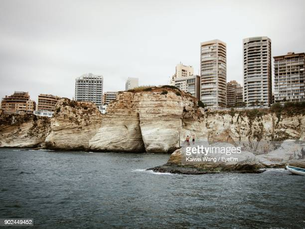 Sea By Cliff Against Modern Buildings In City