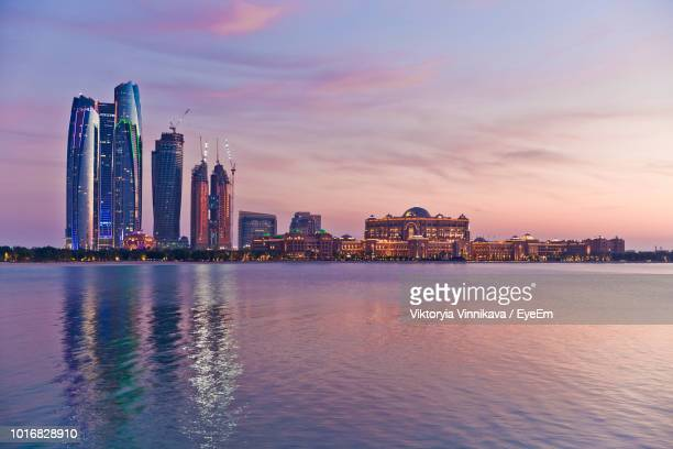 sea by illuminated city buildings against sky during sunset - abu dhabi fotografías e imágenes de stock