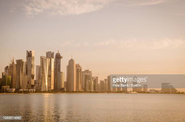 sea by modern buildings against sky in city - qatar stock pictures, royalty-free photos & images