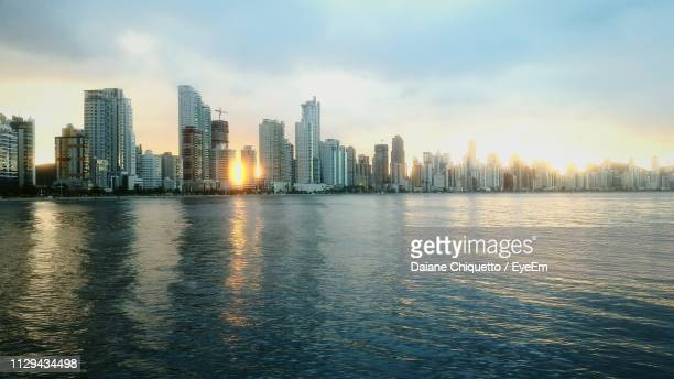 sea by modern buildings against sky in city - praia stock pictures, royalty-free photos & images