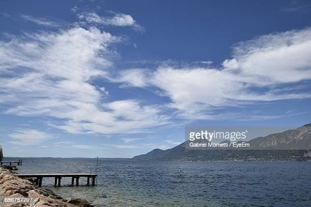 Sea By Mountain With Sky In Background