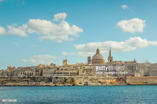 sea by town against sky - valletta stock pictures, royalty-free photos & images