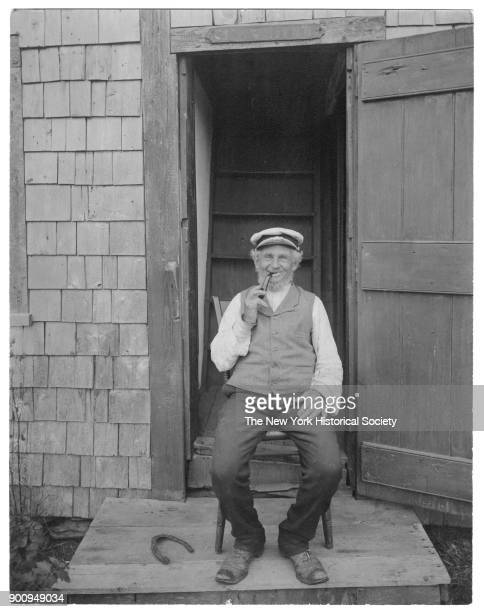 Sea Captain Billy Bowen seated in front of open door with pipe captain's hat horseshoe by his feet Nantucket Massachusetts 1907