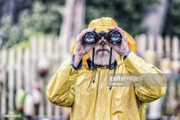 Sea Captain Looking at Camera Through Binoculars
