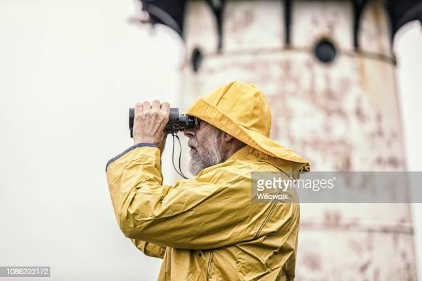 sea captain looking through binoculars near lighthouse - yellow hat stock pictures, royalty-free photos & images