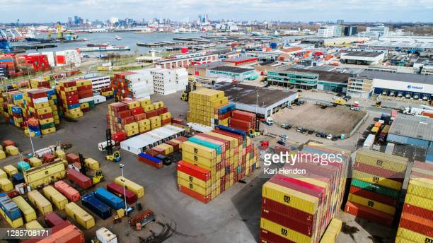 sea containers stacked up in a port - rotterdam stock-fotos und bilder