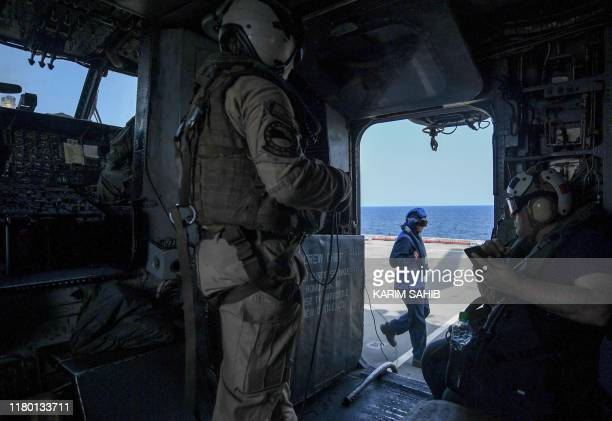 Sea Dragon helicopter crew member looks on as they prepare for takeoff from Britain's RFA Cardigan Bay landing ship in the Gulf waters off Bahrain...