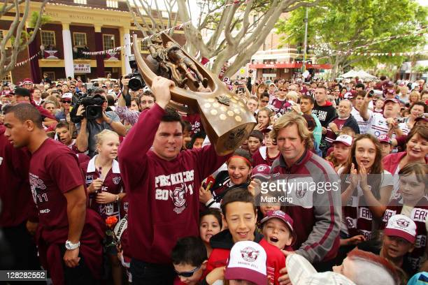 Sea Eagles captain Jamie Lyon holds up the NRL Premiership trophy in front of fans as coach Des Hasler looks on during the Manly Warringah Sea Eagles...