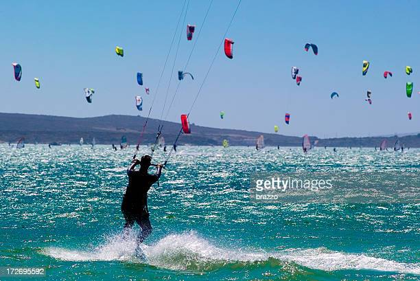 A sea full of kitesurfers with one seen from the rear