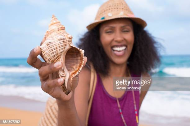 sea gift. seashell at human's hand. - conch shell stock pictures, royalty-free photos & images