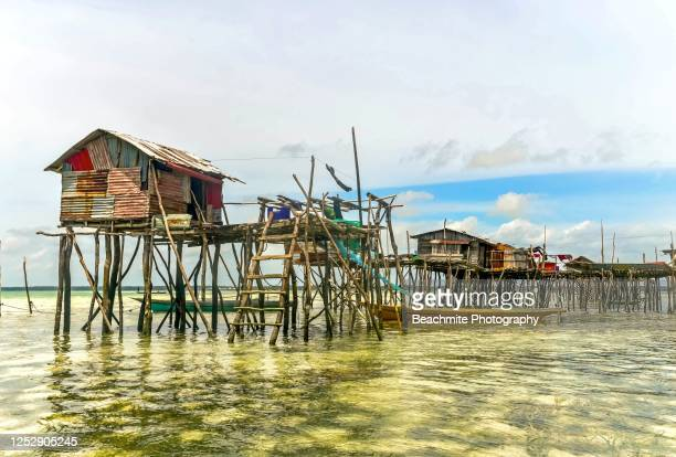 sea gypsies traditional stilt houses amidst crystal clear waters of omadal island, semporna, sabah - island of borneo stock pictures, royalty-free photos & images