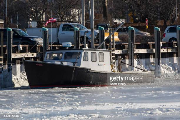 Sea ice surrounds a boat in Rock Harbor on January 3 2018 in Orleans Massachusetts A winter storm is hitting the east coast from Florida to New...