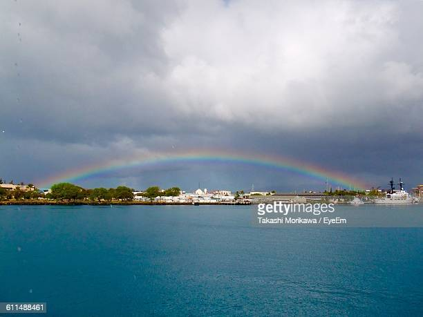 sea in front of city against rainbow in cloudy sky - rainy season stock pictures, royalty-free photos & images