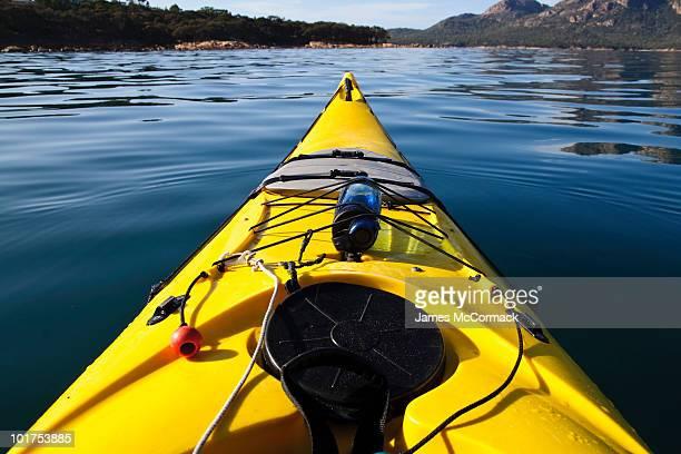 A sea kayak on a calm morning heads into Coles Bay, Freycinet National Park, Tasmania, Australia.