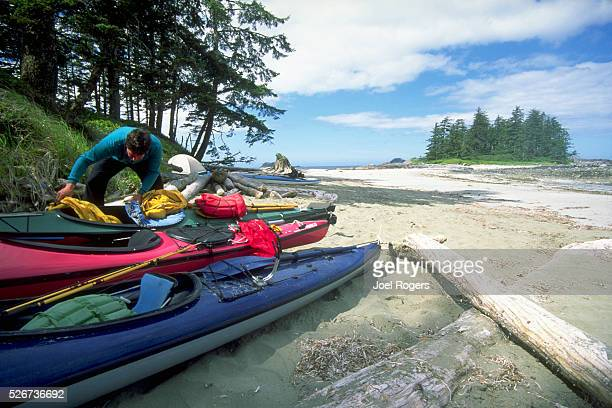 A sea kayaker looks through equipment in his kayak near a camp on the beach Brooks Peninsula Vancouver Island British Columbia