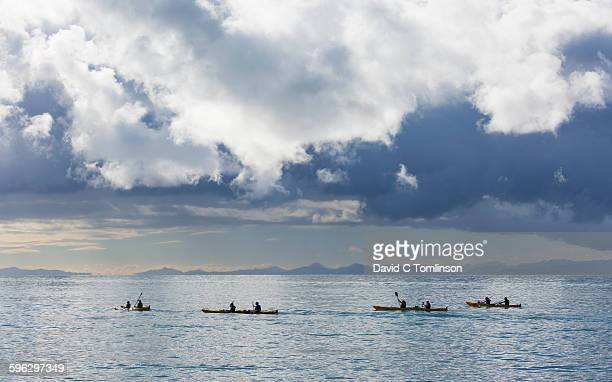 Sea kayaking beneath a stormy sky, Marahau