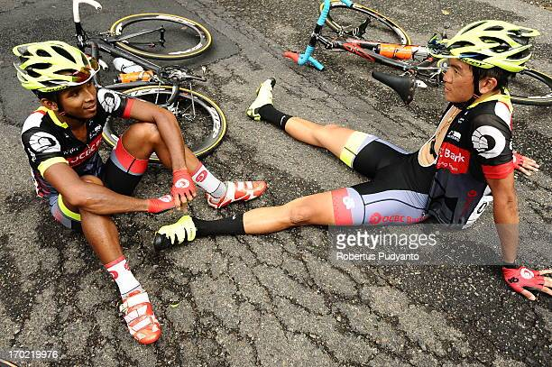 CONTENT] Sea Keong Loh and Ahmad Haidar Anuawar of OCBC Singapore Continental Cycling Team rest for a while because a fallen tree blocking the road...