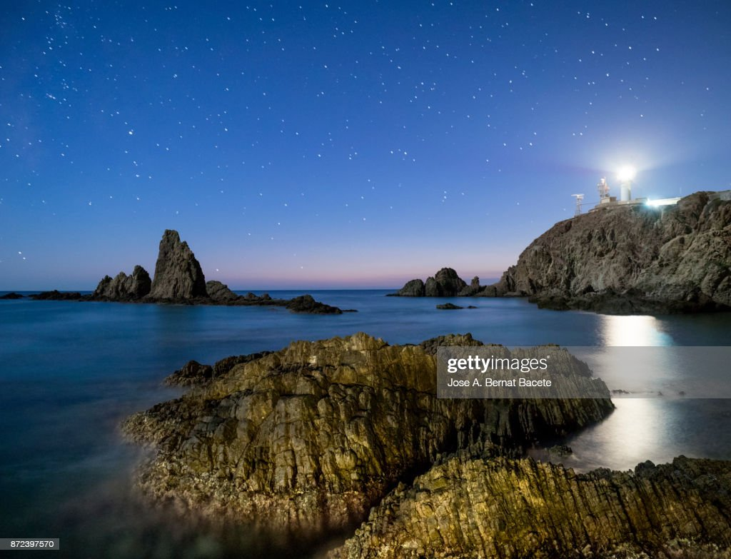 Sea Landscape At Night With Reef Rocks In The Water And A Lighthouse Illuminating Beach Of Stars Blue Sky Cabo De Gata