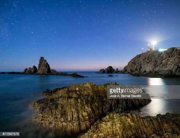 Sea landscape at night, with reef rocks in the water and a lighthouse illuminating the beach, a night of stars with blue sky. Cabo de Gata - Nijar Natural Park, Sirens reef,  Biosphere Reserve, Almeria,  Andalusia, Spain