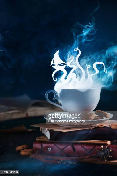 Sea monster, giant octopus silhouette shining in a steaming teacup. Dreamer or reader coffee with books.