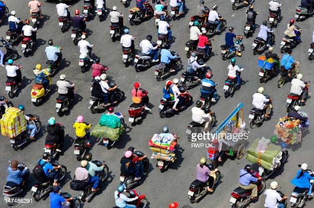 a sea of mopeds during rush hour in central saigon - ho chi minh city stock pictures, royalty-free photos & images
