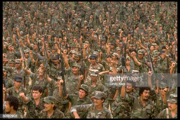 Sea of Nicaraguan contra rebels raising clenched fists shouting wearing fervent expressions at/nr camp in Yamales Honduras
