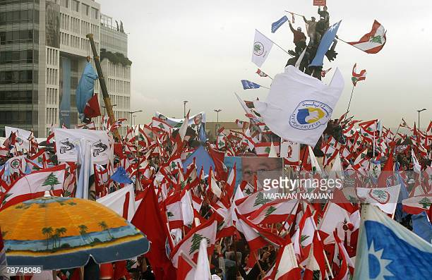 A sea of red white and green Lebanese flags flutter under the rain as people gather in Beirut's Martyr's Square on February 14 to commemorate the...