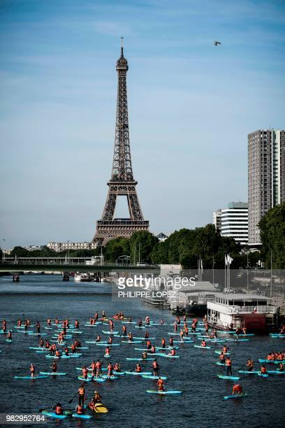 Sea rescuers paddle during a nautical parade on the Seine river in Paris on June 24 2018 a day after the national sea rescuers' day