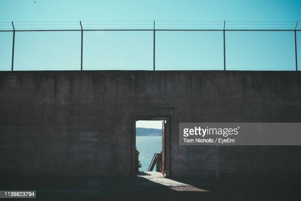 sea seen through door amidst wall - prison stock pictures, royalty-free photos & images