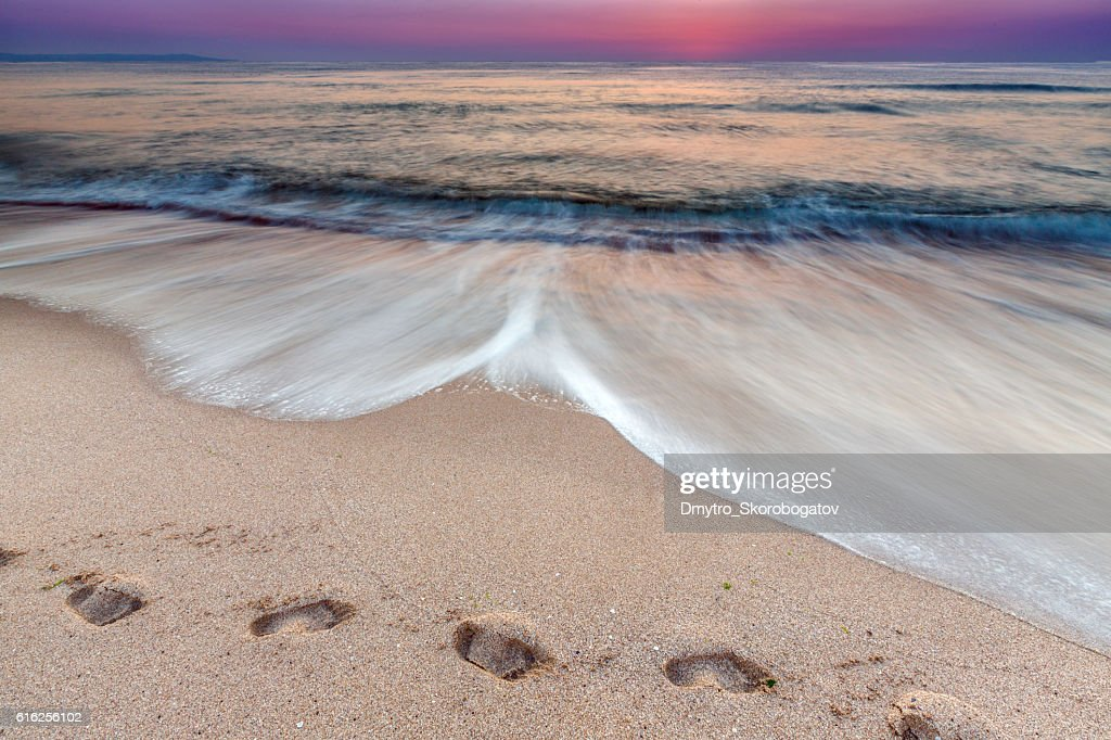 sea shore with a sandy beach with traces of feet : Stock Photo