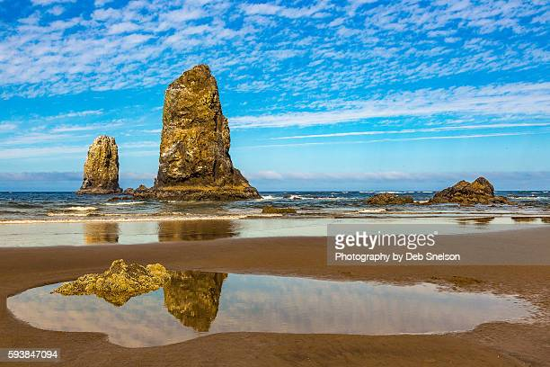 sea stacks reflected in a tide poll on cannon beach oregon - oregon coast stock pictures, royalty-free photos & images