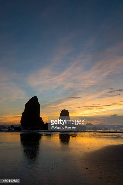 Sea stacks silhouetted at sunset during low tide at Cannon Beach on the Northern Oregon Coast USA