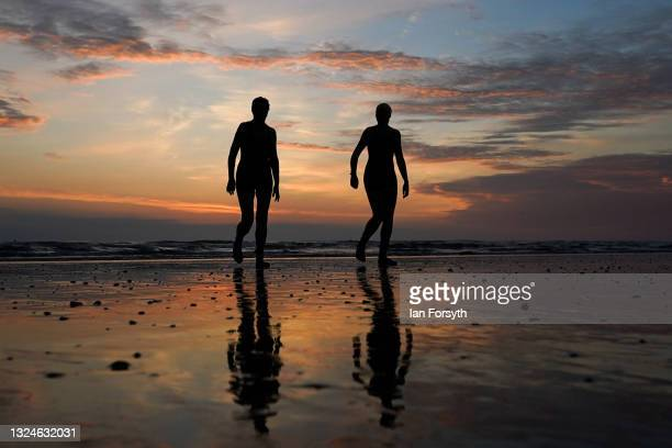Sea swimmers walk from the water after a swim on the morning of the summer solstice at Saltburn beach on June 21, 2021 in Saltburn-by-the-Sea,...