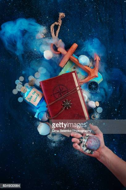 Sea themed travelers essentials still life with wooden anchor, compass, notebook, seashells and sand