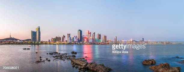 sea view of illuminatedcbd in qingdao, china - qingdao beach stock pictures, royalty-free photos & images