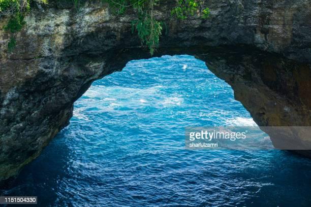 sea view through rocky arch at nusa penida, bali, indonesia. - shaifulzamri imagens e fotografias de stock