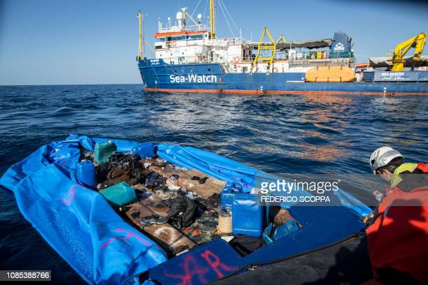 A Sea Watch 3 crew member marks with spray paint a rubber boat that the NGO destroyed after rescuing 47 migrants that were onboard during a rescue...