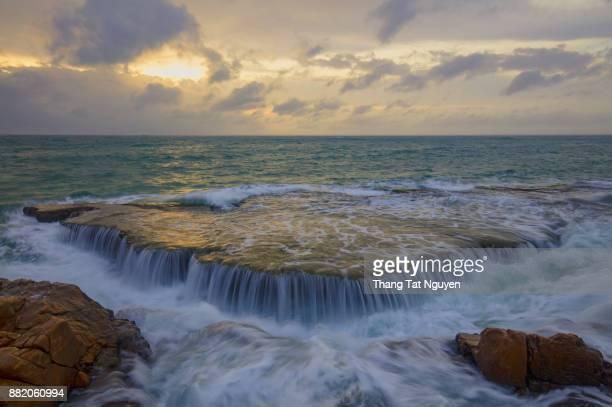 Sea waterfall over rock at dawn