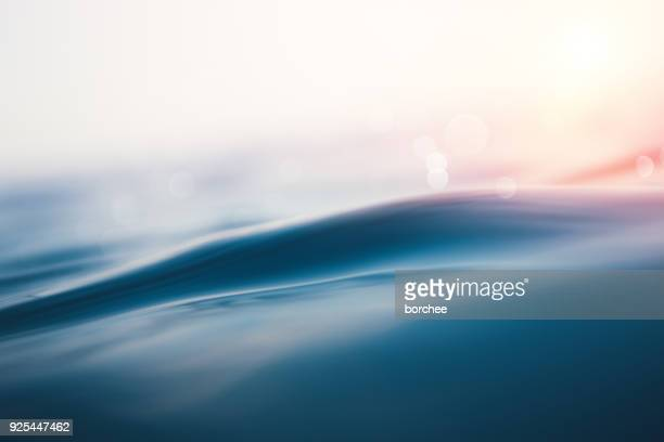 sea wave at sunset - acqua foto e immagini stock