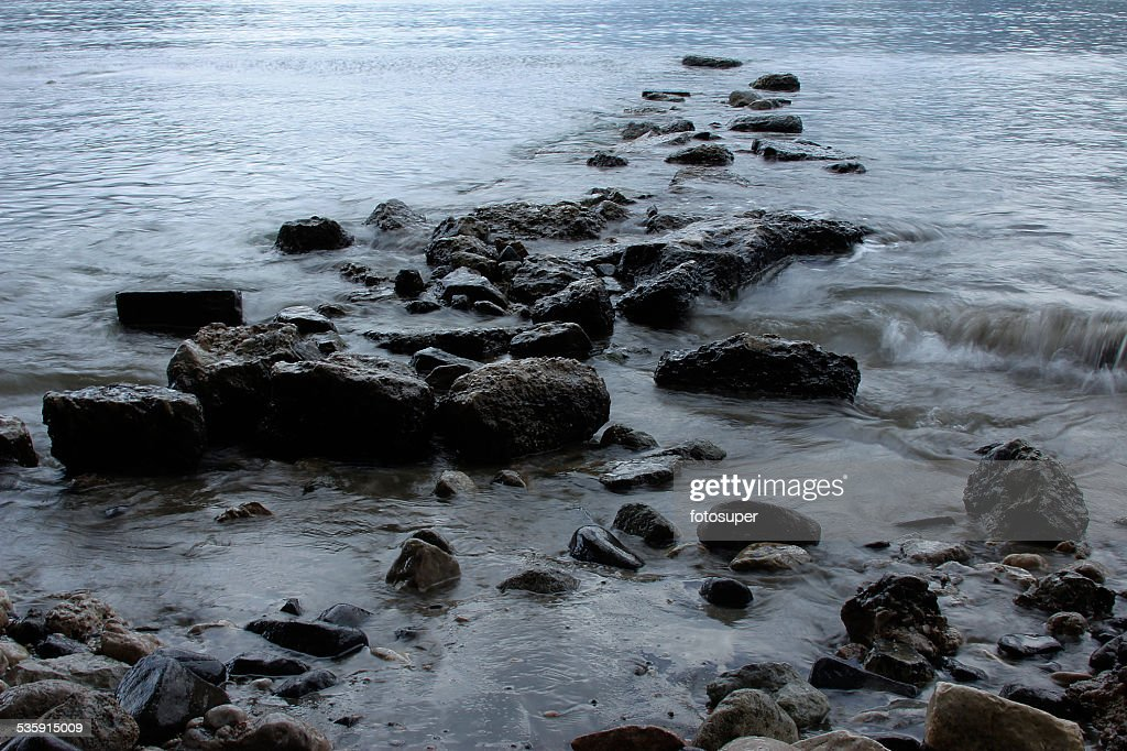sea ​​wave beach sand stones and long exposure : Stock Photo